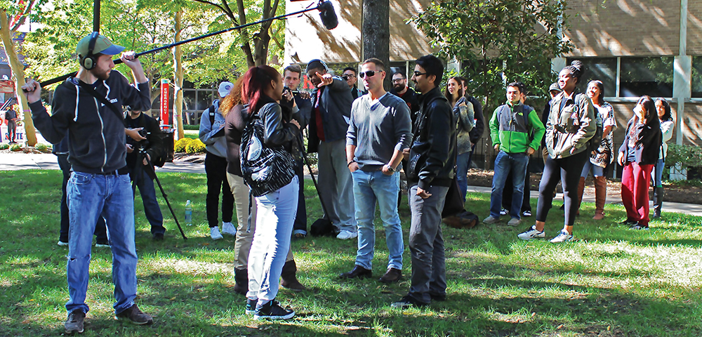 Photo outdoors of students working on a film scene