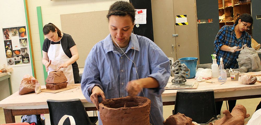 Student working with ceramic clay