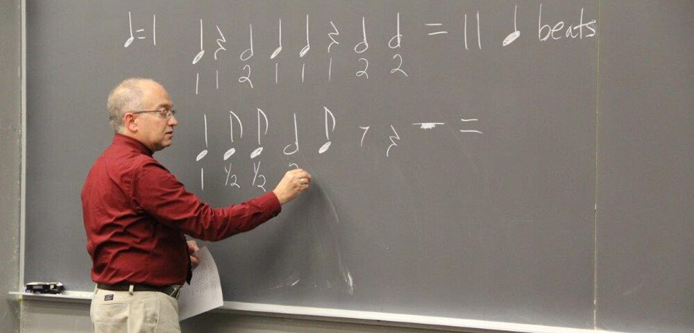 photo of Dr Schiavo at blackboard drawing notes