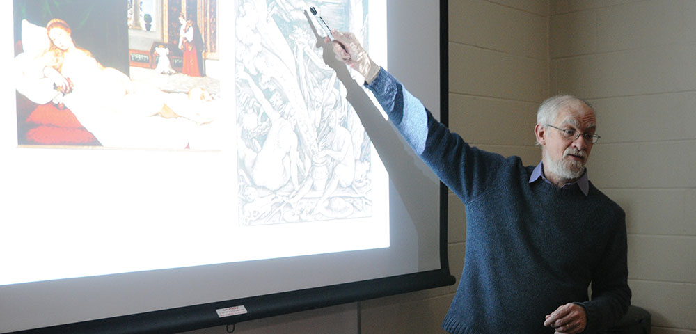 Photo of professor pointing to presentation on a screen